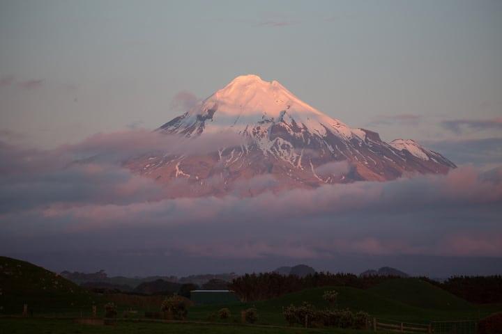 Le Taranaki au sommet enneigé dans les nuages